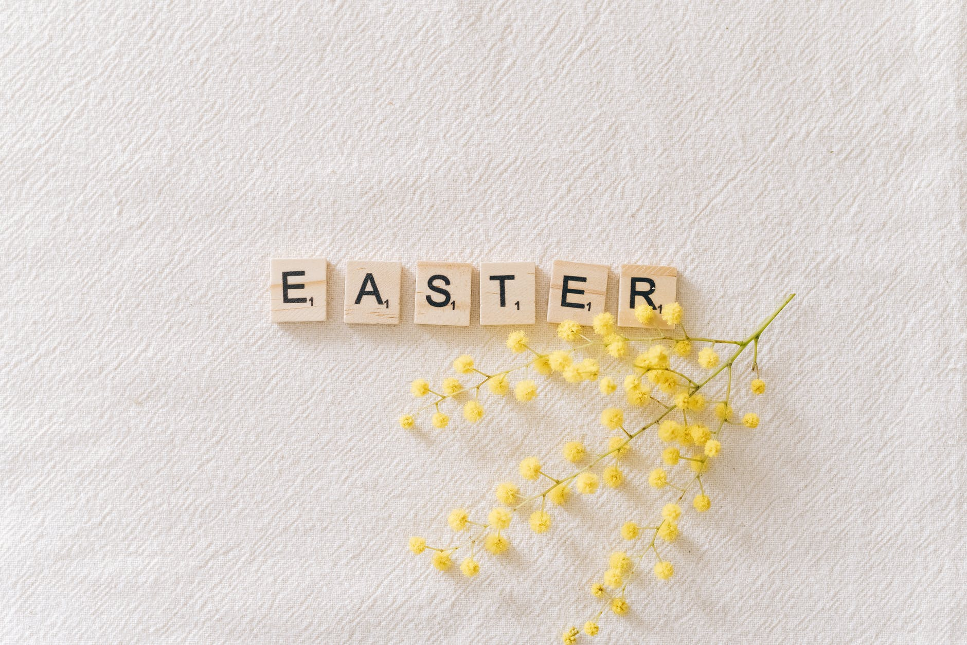 easter text on gray surface beside yellow flowers